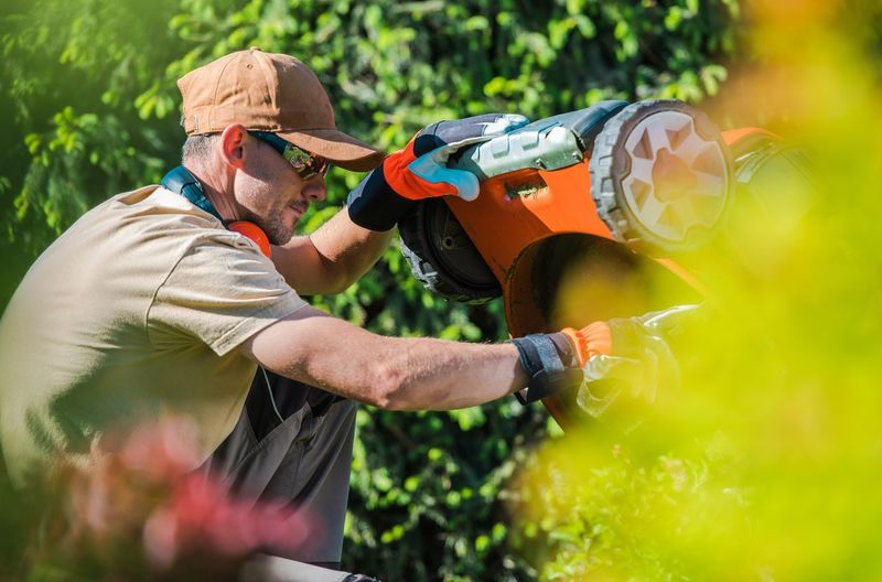 Man checking lawn mover in yard