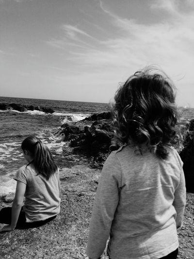 Rear View Of Siblings At Beach Against Sky