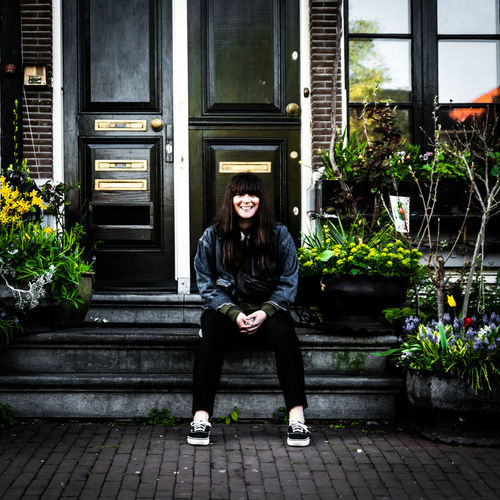 Portrait of teenage girl sitting on potted plant against building