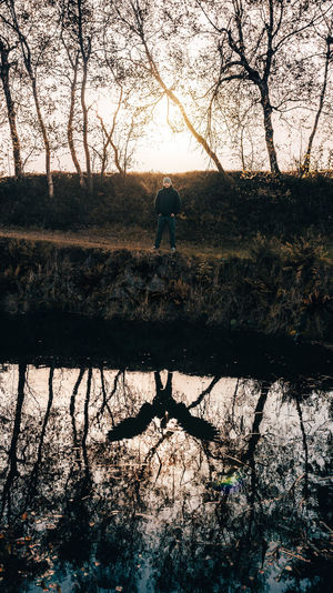 Silhouette man standing by bare tree against lake
