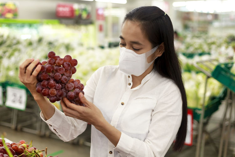 Close-up of woman wearing mask holding grapes
