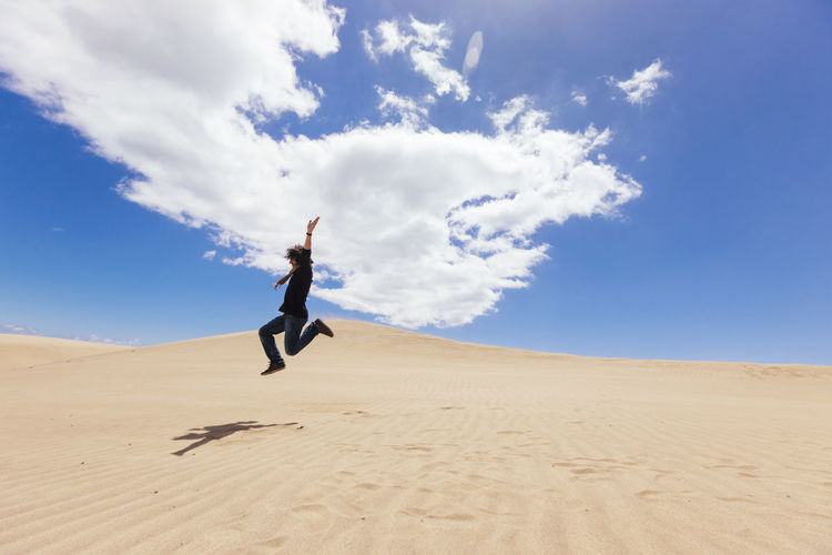 Man jumping on sand at desert against sky