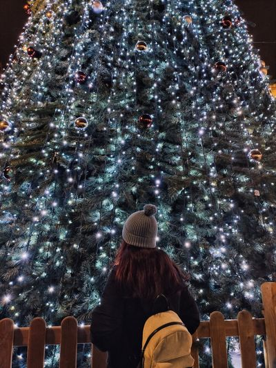Rear view of woman standing against christmas tree at night