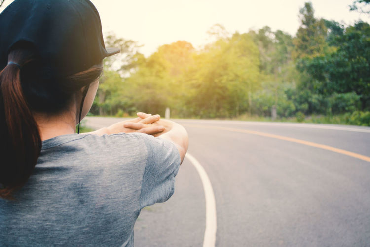 Rear view of woman stretching hands on country road