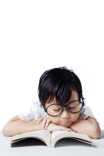 Boy Wearing Eyeglasses Studying On Table Against White Background