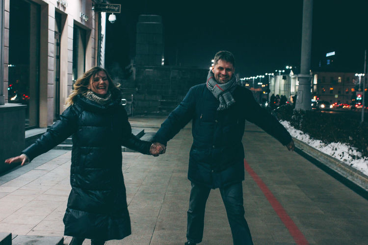Young couple standing on street at night