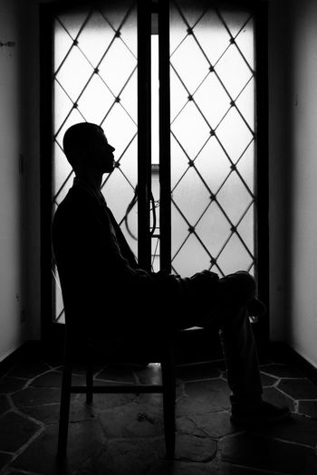 Lightening your thoughts. Sitting Indoors  One Person Window Full Length Chair Silhouette Real People Day Men Silhouettes Blackandwhite Door Light And Shadow Natural Light Lights And Shadows Person People Welcome To Black Black And White Friday