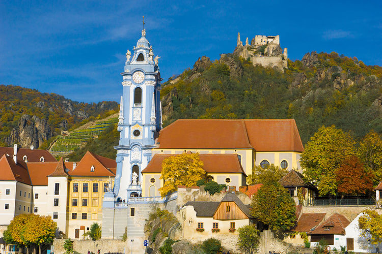 Austria Architecture Blue Blue Church Building Exterior Built Structure Castle Cathedral Church Cross Day Durstein, House Low Angle View Outdoors Place Of Worship Religion Residential Structure Sky Spirituality Sunlight Tree