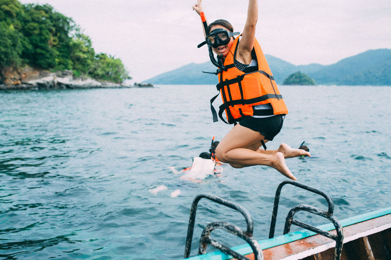 Full length portrait of woman jumping into sea