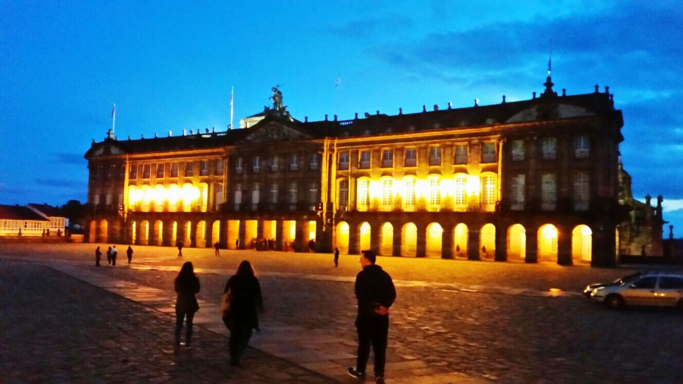 architecture, built structure, illuminated, travel destinations, building exterior, city, silhouette, tourism, walking, government, sunset, history, sky, outdoors, night, people, city gate, adult
