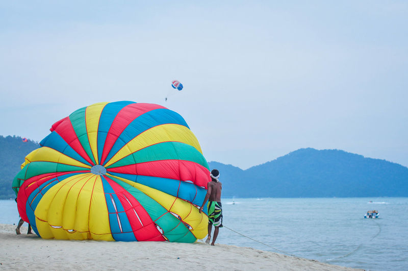 Man with parachute standing at beach against sky