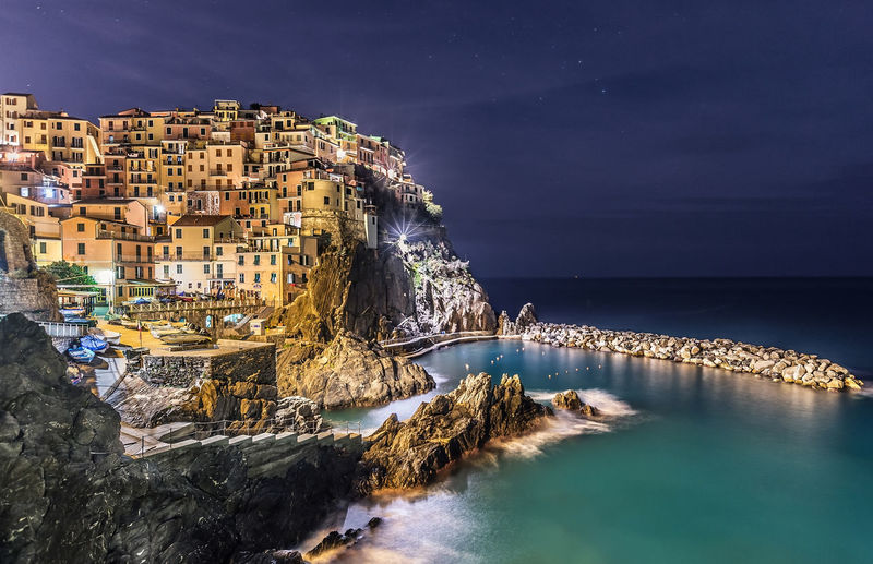 Panoramic shot of illuminated buildings by sea against sky