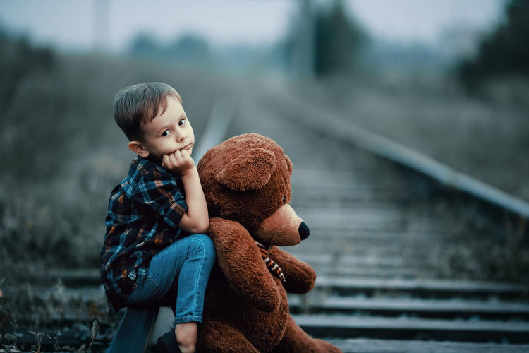 Boy with teddy bear sitting on railroad track