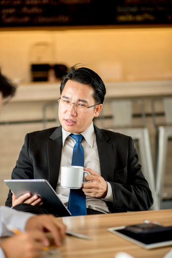 Business Businessman Coffee - Drink Coffee Cup Communication Connection Convenience Corporate Business Digital Tablet Eyeglasses  Food And Drink Front View Holding Indoors  Laptop Mature Adult Mature Men One Man Only One Person Sitting Suit Technology Using Laptop Well-dressed Wireless Technology