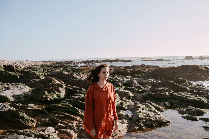 Portrait of young woman standing on rock by sea against clear sky