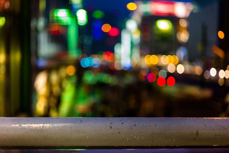 Close-up of wet illuminated railing in city at night