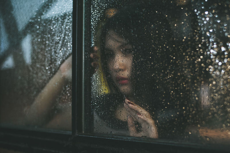 Young Woman Sitting In Car During Rainy Season