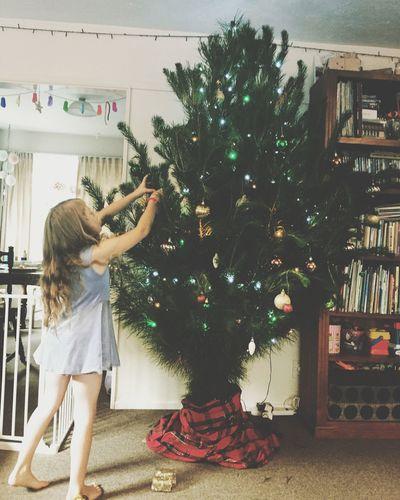 Girl decorating christmas tree at home