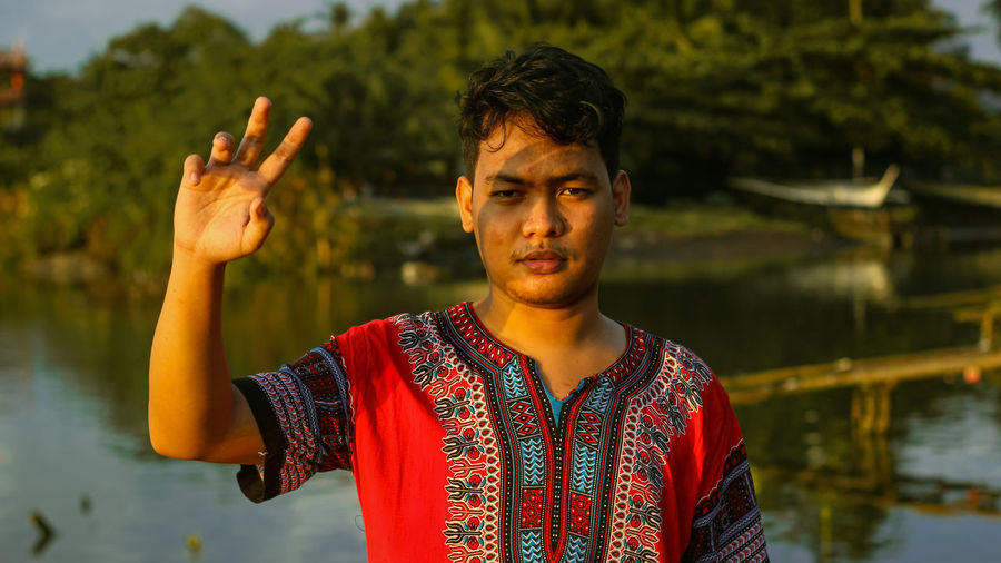 Portrait of young filipino/asian man standing in lake