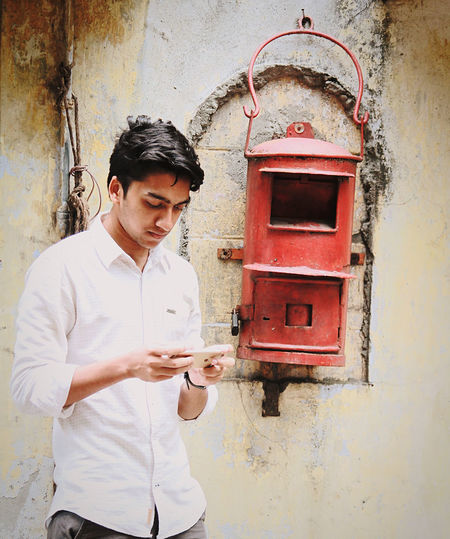 Young man using smart phone while standing against wall