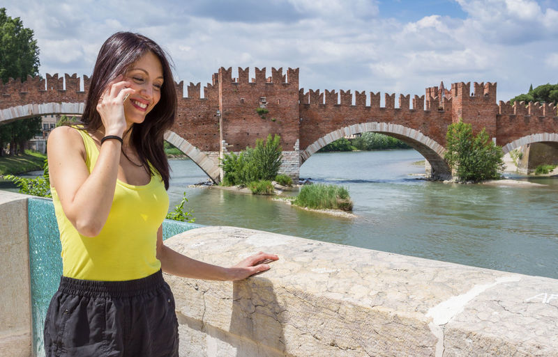 Beautiful woman talking on mobile phone while standing by scaliger bridge over adige river