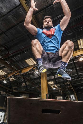 Full Length Of Man Exercising On Box Art Gym