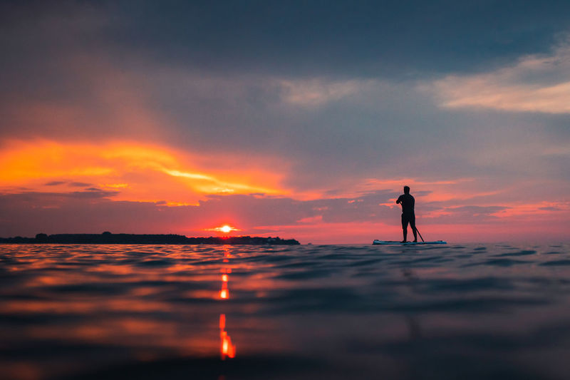 Silhouette man standing on paddleboard against sky during sunset