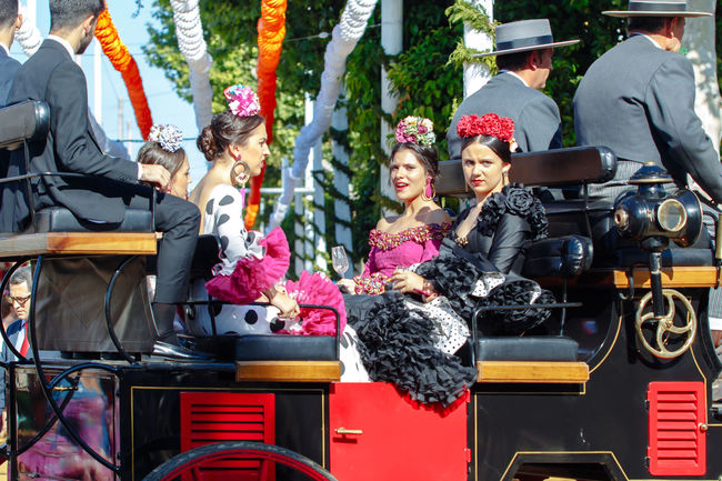 Young and beautiful women on a horse drawn carriage Andalusia Celebration Culture Dancer Dreaming Fair Fashion Feria De Abril Feria De Sevilla 2017 Festival Flamenco Horses People Seville SPAIN Spanish Woman Springtime Traditional Traditional Clothing Woman