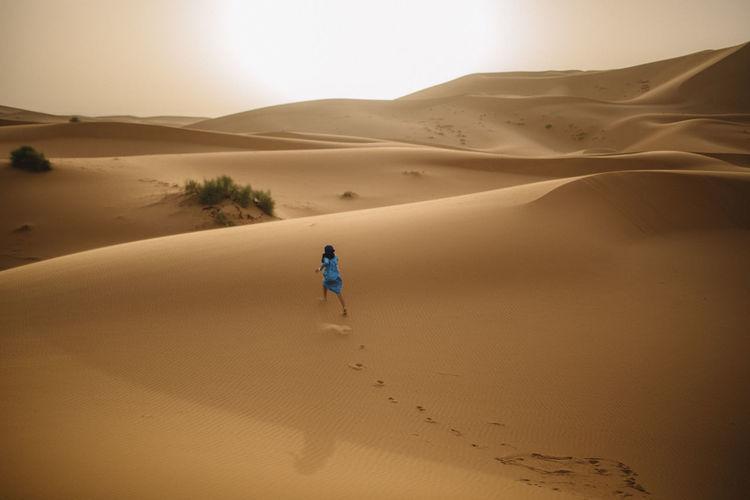 Person on sand dune in desert against sky