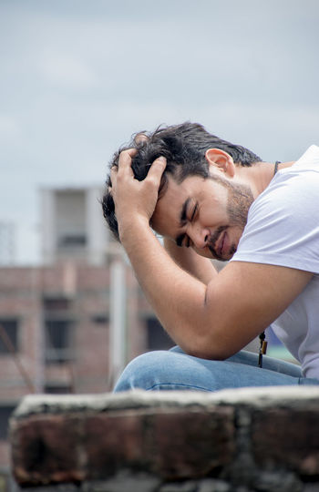 Young man with eyes closed sitting against building