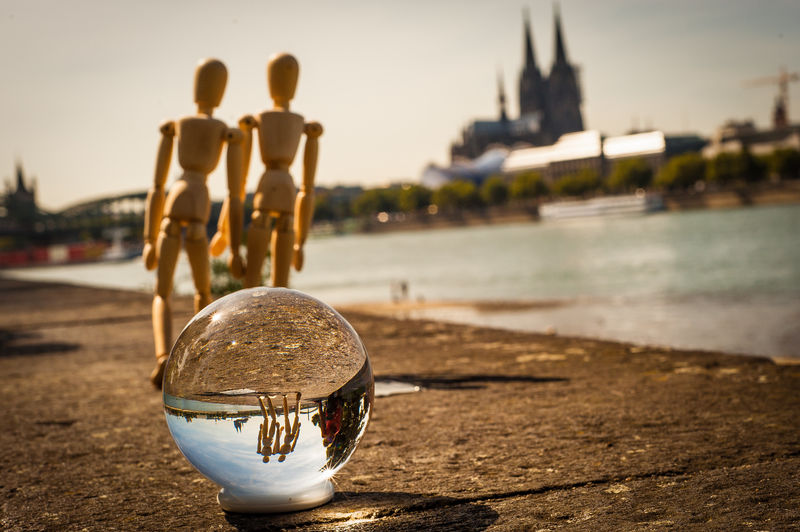 Crystal ball and wooden figurines by rhine river against cologne cathedral in city