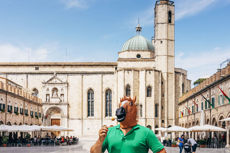 Horse man standing in the middle of the historic square of ascoli piceno eating a fried olive