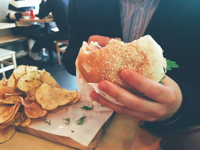 Midsection of man having burger at restaurant