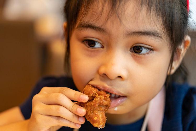 Cute girl eating food at restaurant