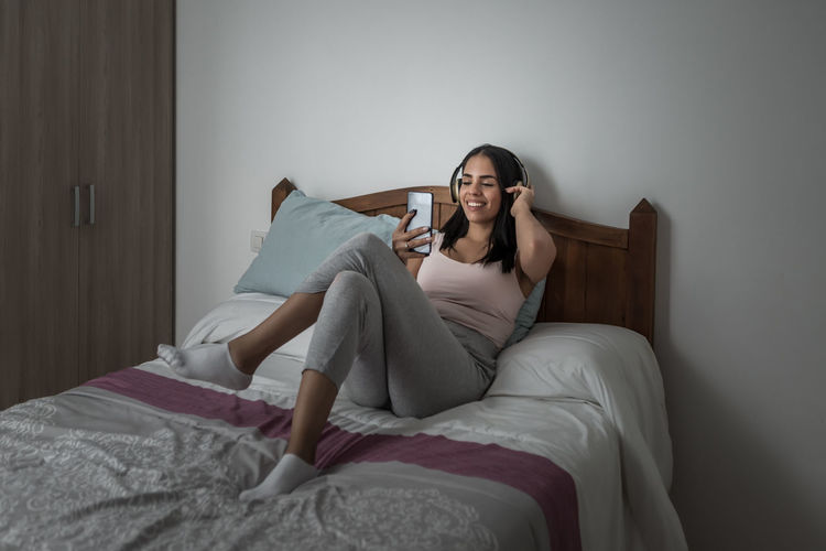 Young woman listening music over phone while lying on bed at home