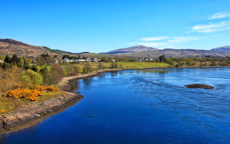 View of Loch Etive and Connel Village, Scotland, UK Beauty In Nature Blue Clear Sky Connel Village Day Etive Grass Lake Landscape Loch Etive Nature No People Outdoors Reflection Rural Scenics Scotland Scottish Highlands Sky Tranquil Scene Tranquility Tree Uk Water Water's Edge