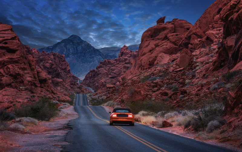 Car on road by mountain against sky