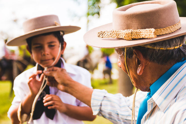 Close-up of grandfather and grandson wearing cowboy hat