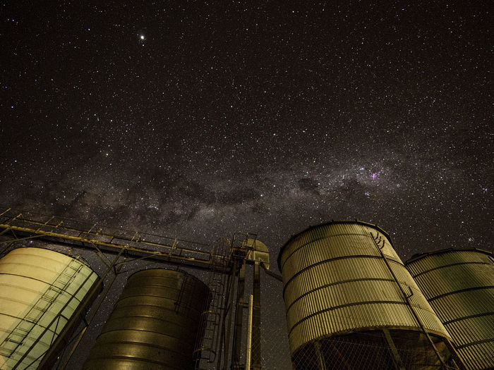 Low angle view of storage tanks against sky at night