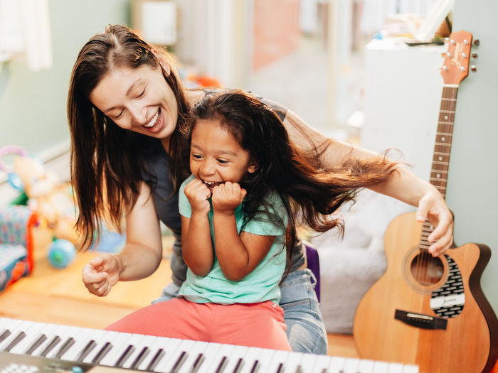 Happy mother teaching piano to daughter at home