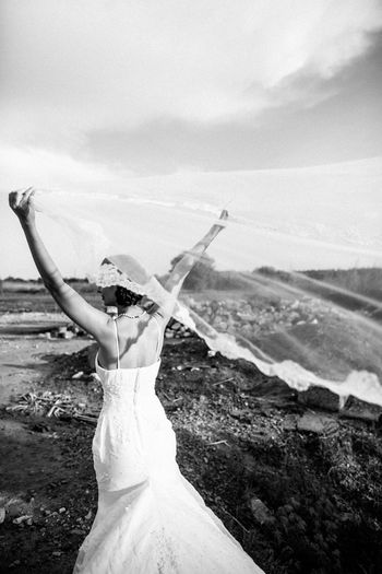 Rear view of bride holding veil on field against sky