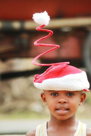 Close-up portrait of cute boy wearing spiral santa hat outdoors