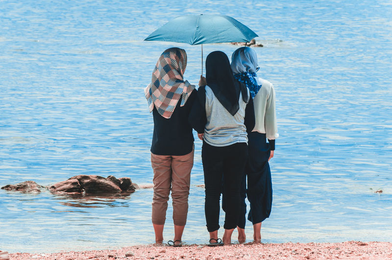 Rear View Of Female Friends With Umbrella Standing At Beach