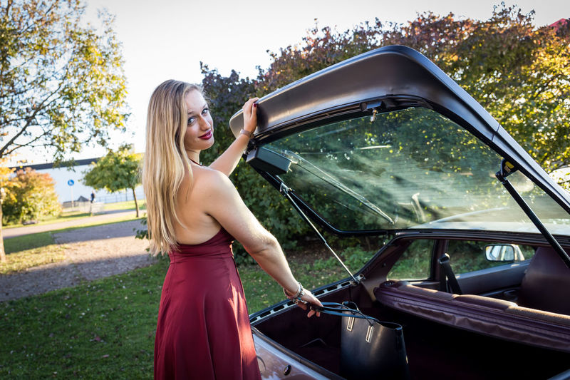 Portrait of young woman removing purse from car trunk