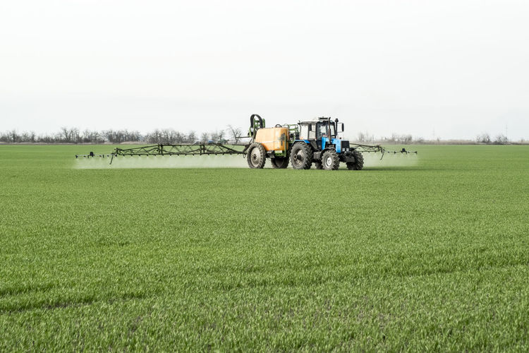 Agricultural machinery spraying insecticides at farm against sky