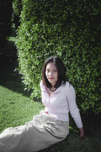 Portrait of young woman sitting on grass against trees