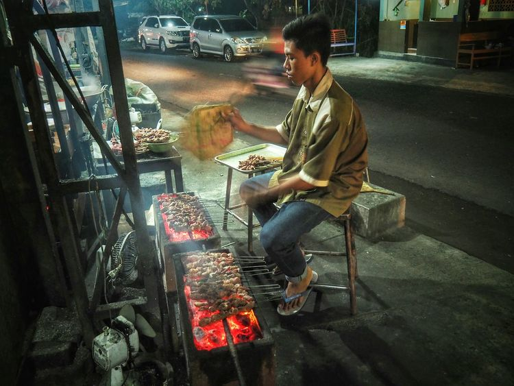 """Sate Klatak is unlike other roasted skewered meats. This Satay is first marinated in a mixture of salt and dash of pepper. The dish consists of small pieces of skewered goat meat which is roasted in an open fire, an act called """"klatak"""" in Javanese, without many other additional ingredients. The skewers are not made of bamboo, as is generally the case with other satay. Instead, the spokes from bicycle wheels are used... Street VendorStreet Photography Nightlife, in Yogyakarta, INDONESIA"""
