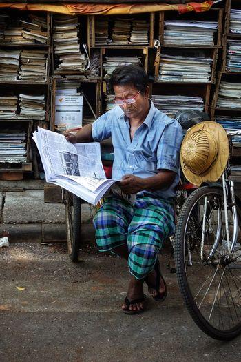 Full length of man reading newspaper at market