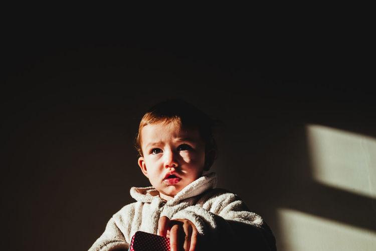 Close-up of boy sitting in darkroom