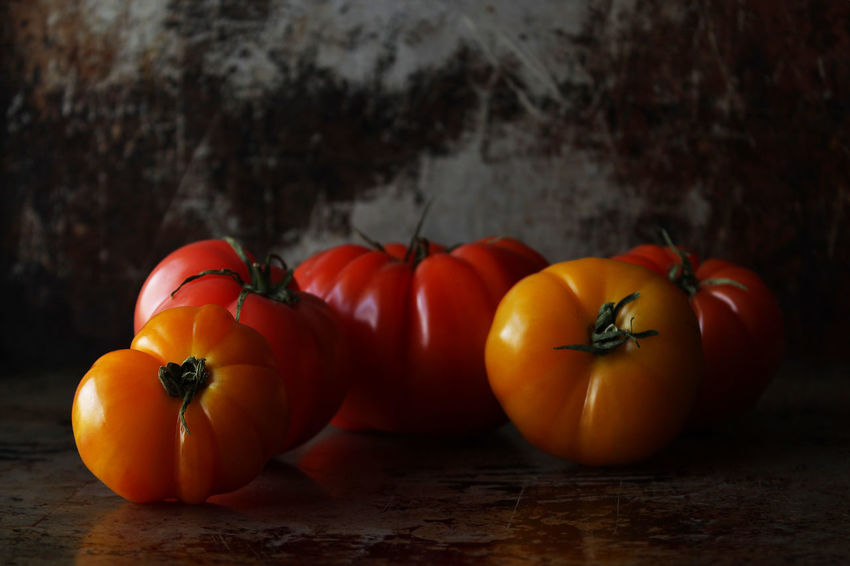 Heirloom tomatoes Heirloom Tomatoes Food And Drink Food Healthy Eating Vegetable Wellbeing Freshness Table Still Life No People Indoors  Tomato Group Of Objects Close-up Focus On Foreground Orange Color Red Nightshade Yellow Dark Copy Space Close Up Multi Colored Rustic Studio Shot
